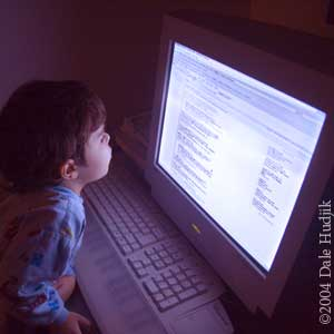 4 year old boy looking at a computer screen