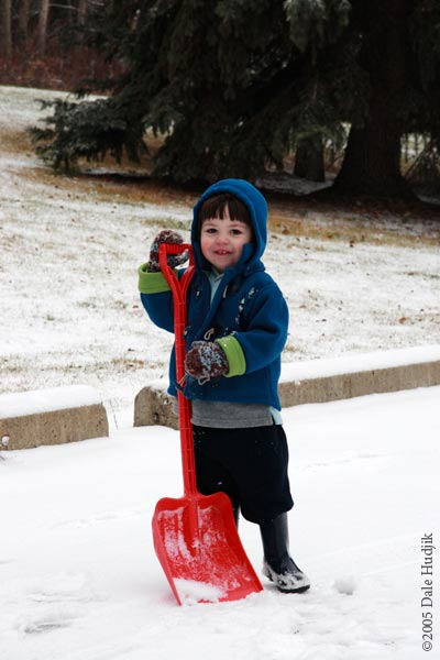 Two year old boy shovelling snow