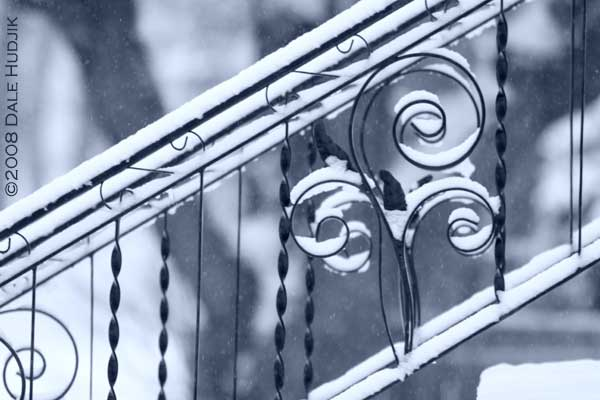 snow on iron railing