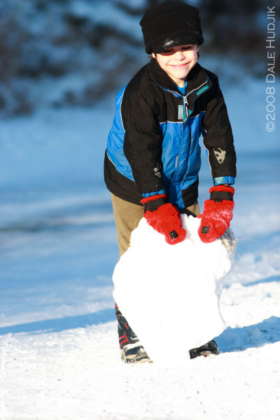 little boy playing in snow